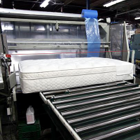 A finished mattress enters the high speed bagging machine.